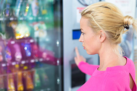 Woman Choosing a Snack from a Vending Machine